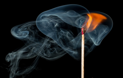A lit match against a black background, symbolizing fire prevention measures for businesses.